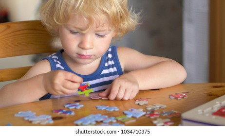 A child playing with a puzzle on table