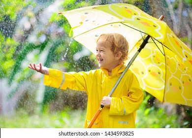 Child playing in the rain on sunny autumn day. Kid under heavy shower with yellow duck umbrella. Little boy with duckling waterproof shoes. Rubber wellies boots. Fall outdoor activity by rainy weather