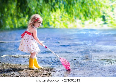 Child playing in a river. Cute little girl in summer dress and rain boots catching fish and frog with a colorful net standing in water. Kids play outdoors. Young explorer and fisherman in wild nature.