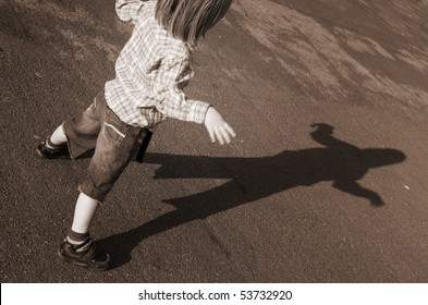 child playing with shadow. boy and his silhouette on road