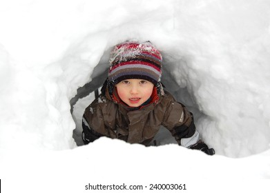 Child playing in snow cave