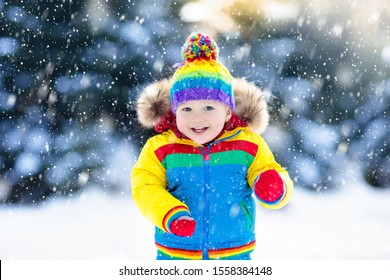 Child playing with snow in winter. Little boy in colorful jacket and knitted hat catching snowflakes in winter park on Christmas. Kids play and jump in snowy forest. Children catch snow flakes