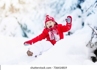 Child playing with snow in winter. Little boy in colorful jacket and knitted hat catching snowflakes in winter park on Christmas. Kids play and jump in snowy forest. Toddler jumping on snowdrift.