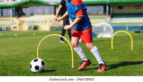 Child playing soccer ball on practice unit. School physical education class for kids. Football sports training camp. Exercise class for sporty boys