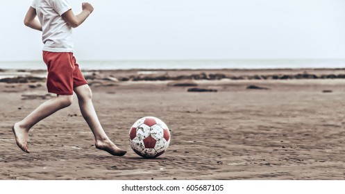 Child playing soccer on the beach