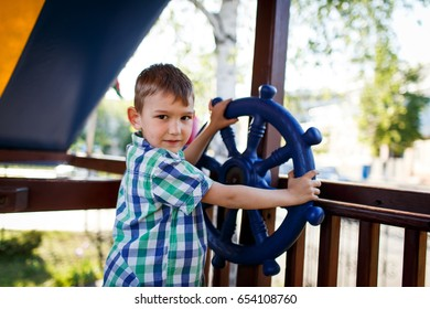 A child playing with a steering wheel on the playground