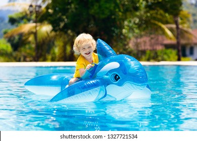 Child playing in swimming pool. Kids learn to swim. Little baby boy with inflatable toy float playing in water on summer vacation in tropical resort. Kid with toy dolphin on beach holiday.