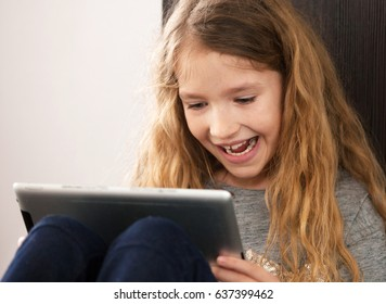 Child playing at tablet. Girl with tablet pc at home