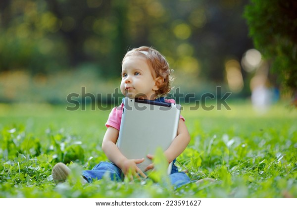 Child playing with tablet outdoors. Cheerful child with a portable PC in your hands. The kid looks away.