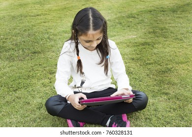 Child playing with tablet pc on green grass