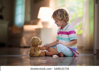 Child playing with teddy bear. Little boy hugging his favorite toy. Kid and stuffed animal at home. Toddler sitting on the floor of living room with big window at sun set. Kids play indoors.