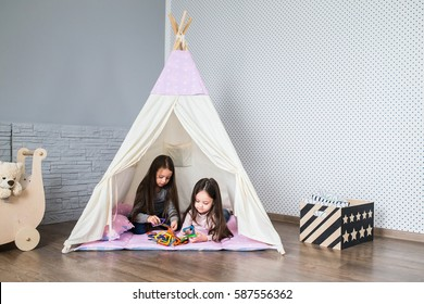 Child playing with a teepee