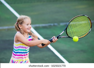 Child playing tennis on outdoor court. Little girl with tennis racket and ball in sport club. Active exercise for kids. Summer activities for children. Training for young kid. Child learning to play.