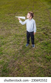 child playing throwing a paper airplane