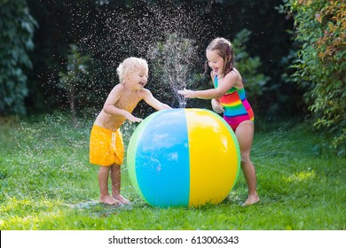 Child playing with toy ball garden sprinkler. Preschooler kid run and jump. Summer outdoor water fun in the backyard. Children play with hose watering flowers. Kids splash on sunny day