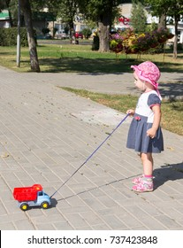 Child playing with a toy car