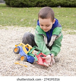 Child playing with toy digger and stones pebbles in playground park.