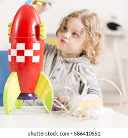 Child playing with toy racket, inhaler device lying on a table