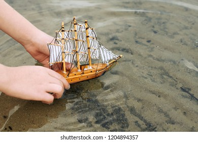 child playing with a toy sailing ship by the river, hand closeup