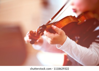 Child playing the violin in a room