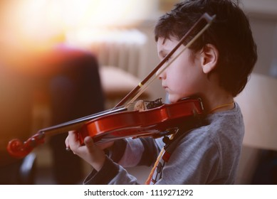 Child playing the violin in  room