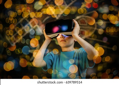 Child playing with a virtual reality headset. Young boy wearing and learning with a VR goggles.
