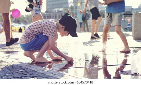 Child playing with water at street fountain