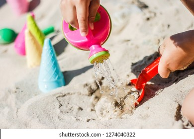 child playing with watering can at the beach of the baltic sea