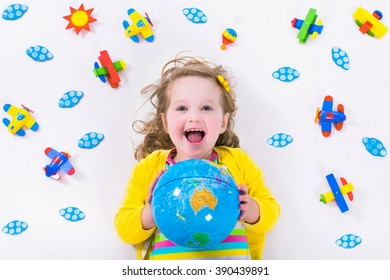 Child playing with wooden airplanes. Preschooler kid flying around the world. Kids traveling and playing. Children at day care or kindergarten. View from above.