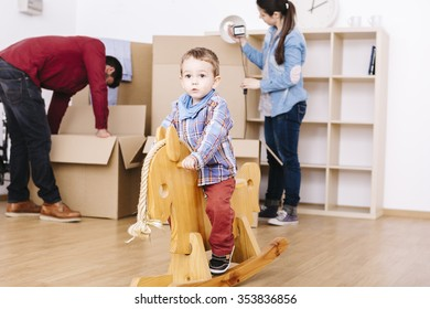 Child playing with a wooden horse while parents make moving