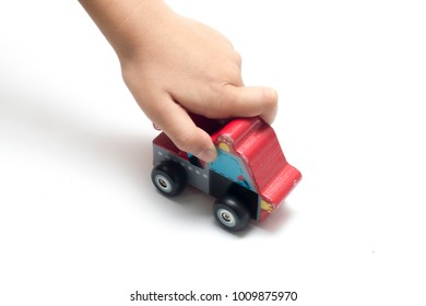 child playing a wooden toy car.