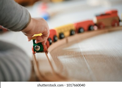 Child playing with wooden train toys. Educational and natural toys, learning through experience concept, creative playing, gross and fine motor skills, educational approach concept.
