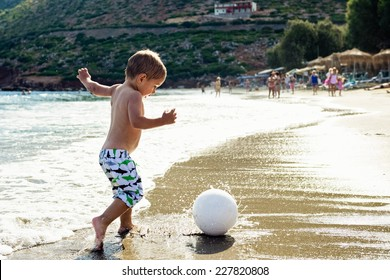 Child plays with a ball on the beach.