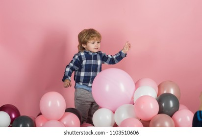 Child plays balloons. Caucasian baby boy plays with baloons at home. Adorable little boy with pink baloon on pink background