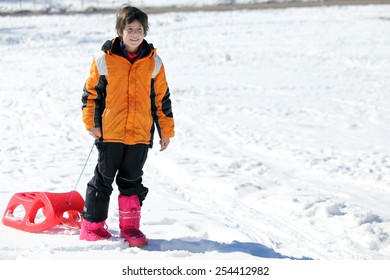 Child plays with bob in the snow in winter