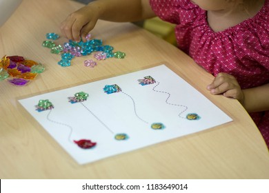 child plays with colorful stones