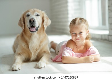 A child plays with a dog at home.