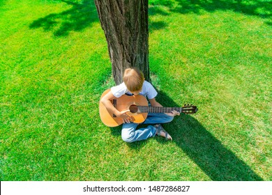 The child plays the guitar in nature, top view.