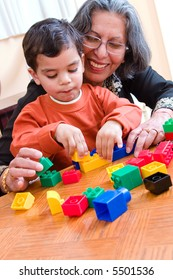 A child plays with his blocks while his grandmother helps him
