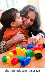 A child plays kisses his grandmother while playing with his toys