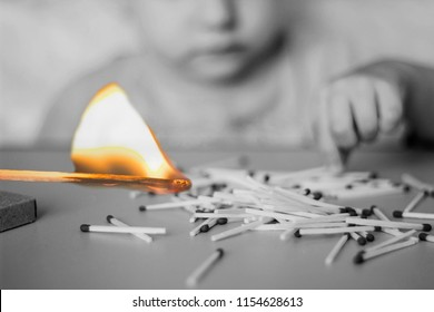 A child plays with matches in the foreground a burning match, a child and matches, a fire, dangerous, black and white