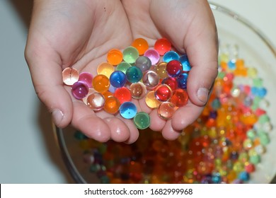 The child plays with multi-colored hydrogel balls.