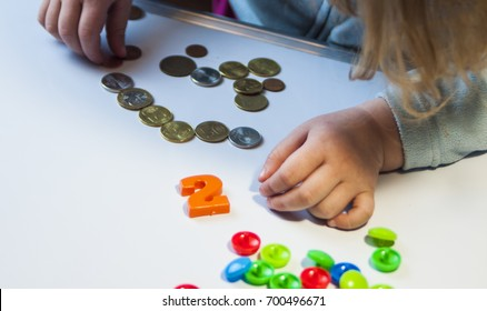 the child plays on the table with pennies and learns to count money