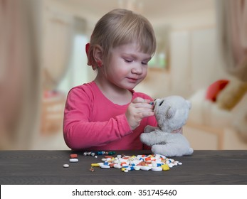 A child plays with pills. Girl feeds pill capsule toy - polar bear cub. Danger game with pills. Bad game. The risk of poisoning