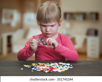 A child plays with pills. Girl gets pill capsule from the blister. Danger game with medication, pills. Risk of poisoning baby