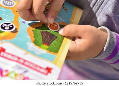 Child plays a pirate quest on a paper map, hands glue a sticker