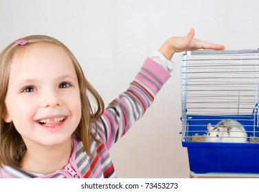 child plays with a rat in a cage