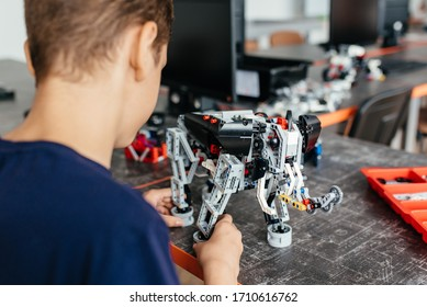 Child plays with a robotic toy assembled from the designer