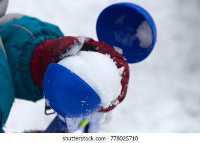 Child plays with snowballs maker