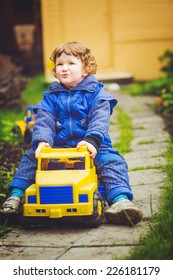 A child plays a toy car on the grass.